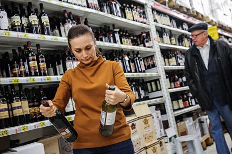 A woman choosing wine at an Auchan hypermarket. Source: Mikhail Pochuyev/TASS