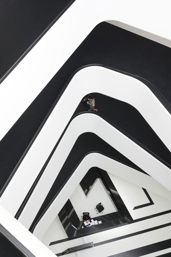 L'atrium est l'élément central du bâtiment. Les lignes entrecroisées complexes des escaliers semblent perforer l'espace noir et blanc minimaliste.
