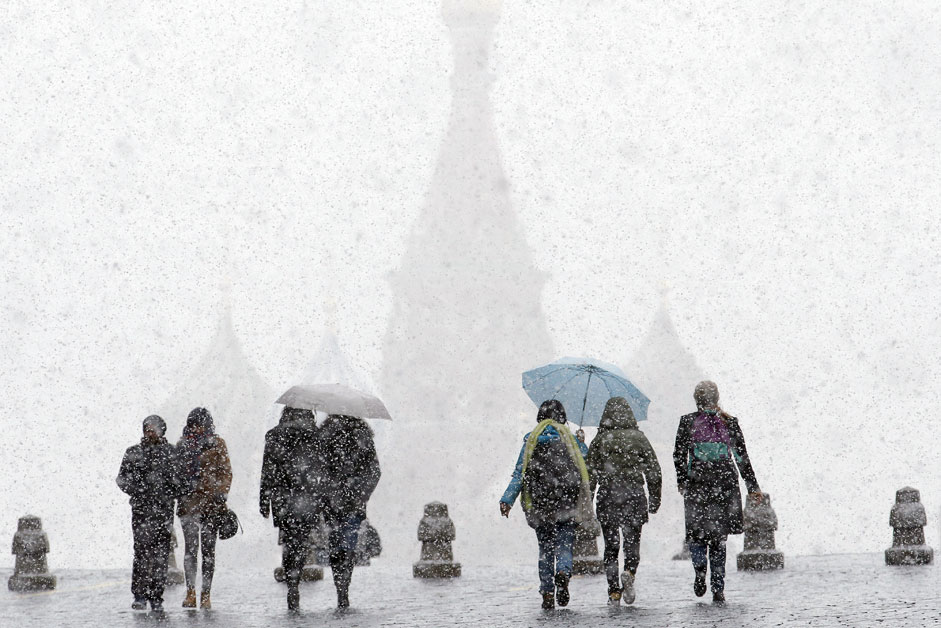 People walk under umbrellas during a snowfall in Red Square, with St. Basil's Cathedral seen in the background, in central Moscow, Russia