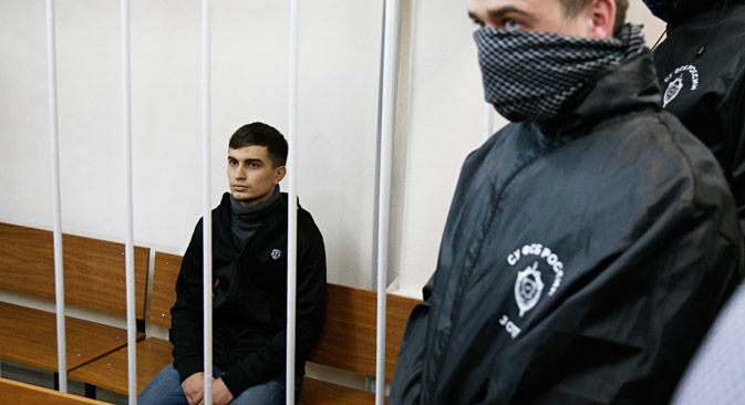 Aslan Baisultanov, a man suspected of plotting a terrorist attack in Moscow, sits in a defendants' cage as two intelligence officials with their faces covered, stand in a court room in Moscow, Oct. 13, 2015. Source: AP