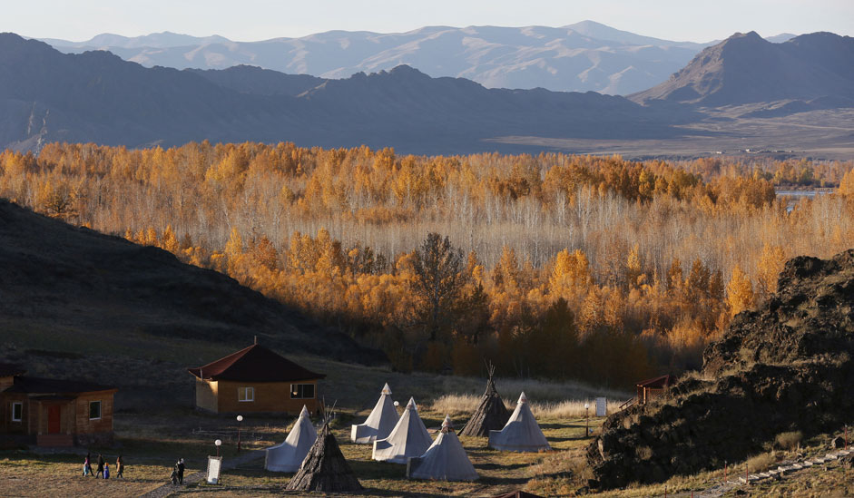 People visit an ethno-cultural complex in the Aldyn Bulak area during sunset on the bank of the Yenisei River outside the village of Ust-Elegest in Tuva region, Southern Siberia, Russia, October 7, 2015. The region is inhabited by Tuvans, historically cattle-herding nomads, who nowadays practise two main confessions - Buddhism and Shamanism.