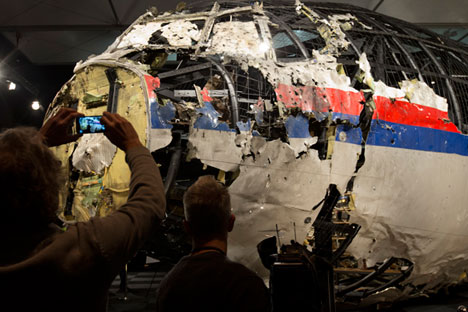 Journalists take images of part of the reconstructed forward section of the fuselage after the presentation of the Dutch Safety Board's final report into what caused MH17 to break up high over Eastern Ukraine last year, Oct. 13, 2015. Source: AP