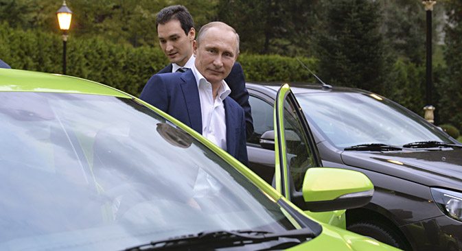 Russian President Vladimir Putin (front) gets into an AvtoVAZ Lada Vesta before driving to attend a session of the Valdai International Discussion Club in Sochi, Russia, October 22, 2015