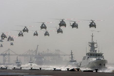 Helikopter AU Indonesia membentuk formasi di atas kapal AL Indonesia yang berlayar selama perayaan hari Angkatan Bersenjata ke-69 yang dipimpim oleh Presiden Susilo Bambang Yudhoyono di kota Surabaya, 7 Oktober 2014.
