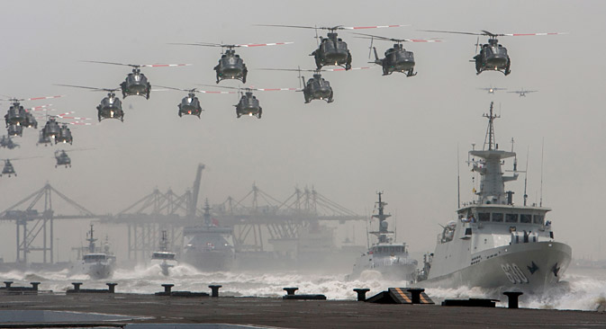 Indonesian air force helicopters fly over navy ships sailing in formation during the celebration of the 69th anniversary of the Indonesian armed forces.