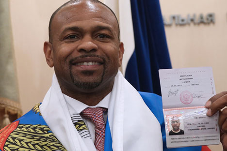 Professional Boxer Roy Jones Jr. holds his Russian passport as he poses for a photograph at an office of the Federal Migration Service.
