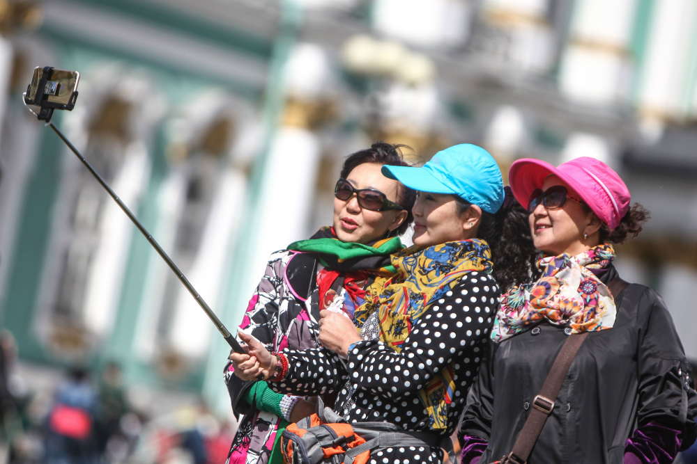 Chinese tourists taking a selfie in front of the Hermitage, St. Petersburg.