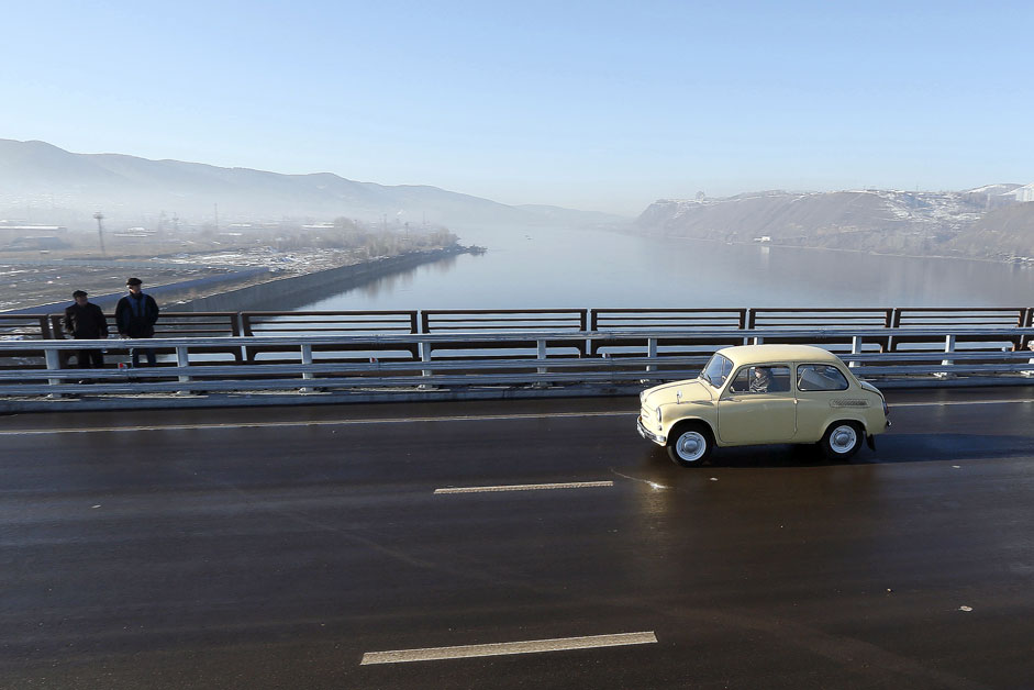 A man drives a Soviet-made Zaporozhets retro car along a new highway bridge during an opening ceremony above the Yenisei River in the Siberian city of Krasnoyarsk, Oct. 29, 2015.