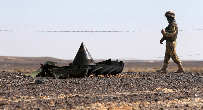 An Egyptian army soldier stands guard near debris from a Russian airliner which crashed at the Hassana area in Arish city, north Egypt, Nov. 1, 2015.
