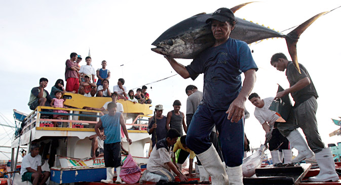 Fishermen and their families watch as a worker carries a yellow fin tuna off a fishing boat at fish at a port in General Santos City, Mindanao, southern Philippines January 10, 2008. The Philippines is one of the biggest tuna producing countries in the world and most of its exports are through General Santos, a port city on the archipelago's southern tip.