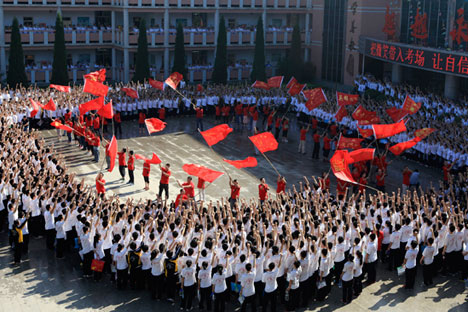 "Students cheer as teachers wave flags before the students take their national college entrance exam in Hengshui, Hebei province, June 7, 2014. According to Xinhua News Agency, about 9.39 million students would take China's national college entrance exams or ""gaokao"" from June 7 to 8, which is a fiercely competitive test that is seen as make-or-break for getting ahead."