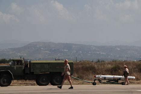 Russian servicemen transport a high-precision Kh-25 missile to a Su-24 aircraft at the Khmeimim airbase in Syria