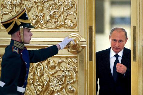 Seorang penjaga kehormatan membukakan pintu saat Presiden Rusia Vladimir Putin (kanan) memasuki aula untuk menghadiri pertemuan dengan anggota Dewan Kepresidenan untuk Masyarakat Sipil dan Hak Asasi Manusia di Kremlin, Moskow, Rusia, 1 Oktober 2015.