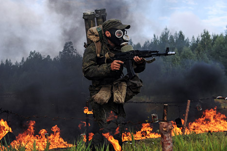 Salah seorang personil tentara NBK Rusia berlari melewati api dengan pakaian khusus NBK selama pelatihan militer tahunan di daerah Sverdlovsk, Rusia, 21 Augustus 2014.
