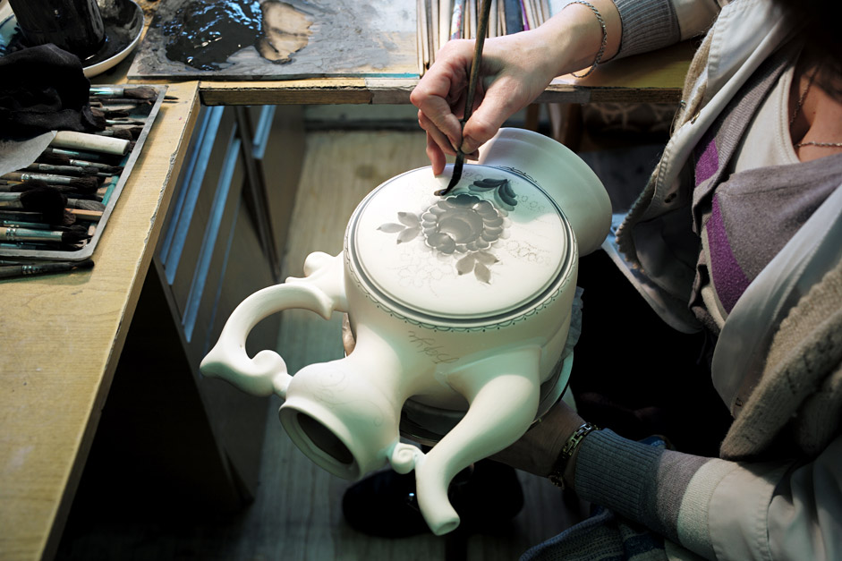 An artist paints a porcelain pitcher at the Moscow Region's Gzhel porcelain factory.