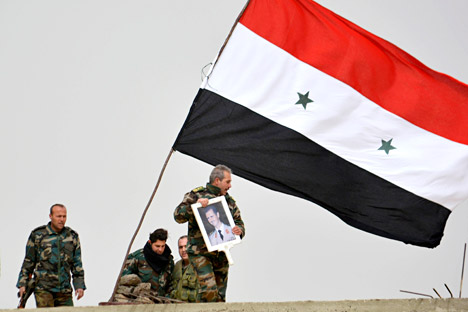 A fighter loyal to Syria's president Bashar Al-Assad holds his picture as fellow fighters rest by a Syrian national flag after gaining control of the area in Deir al-Adas, a town south of Damascus, Daraa countryside February 10, 2015.