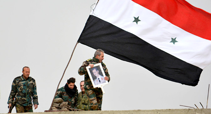 A fighter loyal to Syria's president Bashar Al-Assad holds his picture as fellow fighters rest by a Syrian national flag after gaining control of the area in Deir al-Adas, a town south of Damascus, Daraa countryside February 10, 2015. Syrian government troops and their allies in the Lebanese group Hezbollah pressed a major offensive in southern Syria on Wednesday, taking new ground in a campaign against insurgents who pose one of the biggest remaining threats to Damascus. Syrian state TV broadcast live from Deir al-Adas, a town some 30 km (19 miles) south of Damascus that it said had been captured. The sound of artillery being fired could be heard. The nearby town of Deir Maker was also captured, state TV said. Picture taken February 10, 2015.