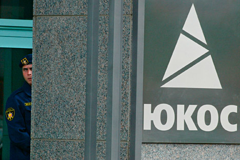 A guard looks from an entrance of Yukos oil company headquarters in Moscow, Thursday, July 22, 2004.