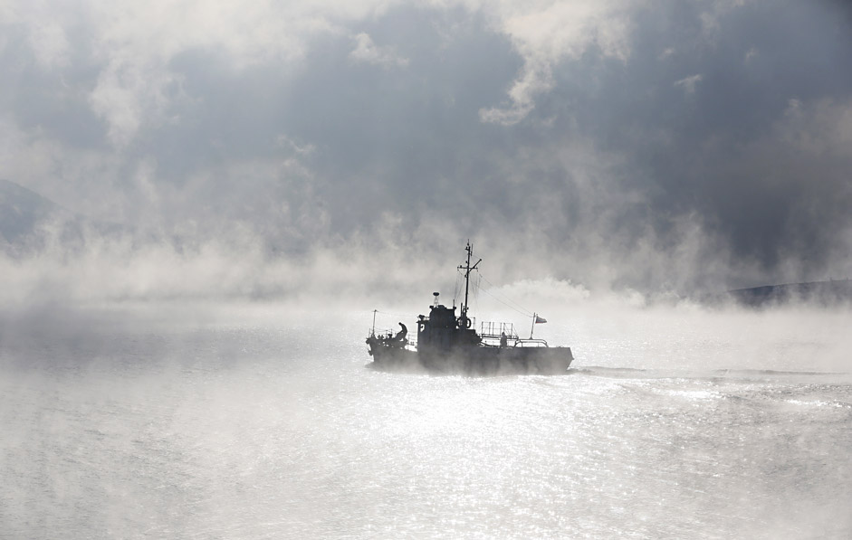 A motor boat travels through the frosty fog along the Yenisei River at air temperature some minus 21 degrees Celsius in the Taiga district outside the Siberian city of Krasnoyarsk, Russia