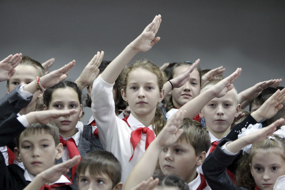 Children, wearing red neckerchiefs, a symbol of the Pioneer Organization, salute while posing for a picture during a ceremony for the inauguration of 18 newly adopted members at a local school in the southern settlement of Kazminskoye in Stavropol region, Russia, November 19, 2015. Early pro-communist youth movements, which appeared in Russia after the 1917 Bolshevik revolution, were reformed into the Pioneer Organization of the Soviet Union. While the organization lost its dominance among students in post-Soviet Russia, some educational institutions and families still carry on this tradition.