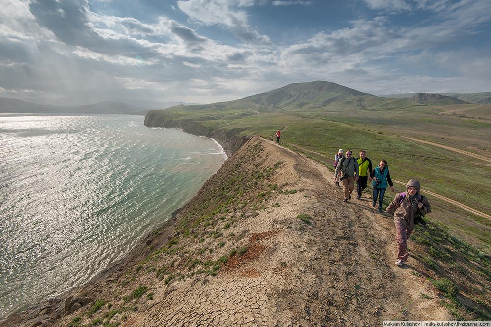 Tikajski zaljev i Rt Kameleon s turistima koji šeću duž morske obale.
