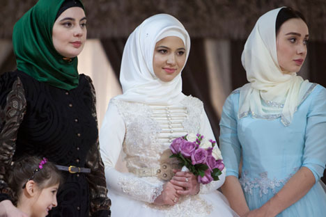 In this Wednesday, Oct. 14, 2015, photo, a Chechen bride dressed in national costume is surrounded by her relatives, as she waits for her wedding ceremony to begin in Grozny, Russia.