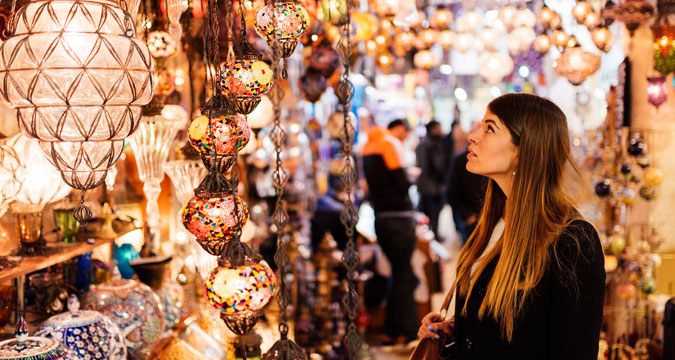Young woman looking at lights on market stall, Istanbul, Turkey.