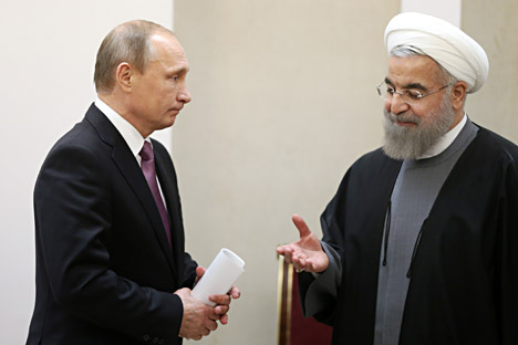 Iran's President Hassan Rouhani, right, makes his way to shake hands with Russian President Vladimir Putin after signing documents during the Gas Exporting Countries Forum (GECF) in Tehran.