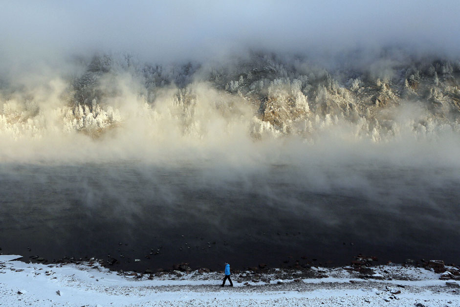 A woman walks along a bank of the Yenisei River covered with a frosty fog, with the air temperature at about minus 26 degrees Celsius (minus 14.8 degrees Fahrenheit), in the Siberian town of Divnogorsk near Krasnoyarsk, Russia