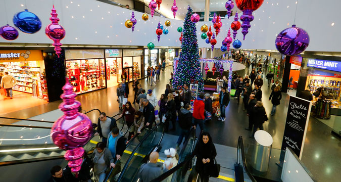 Shoppers walk under Christmas decorations at the Sihlcity shopping mall during a special Sunday sale in Zurich December 22, 2013