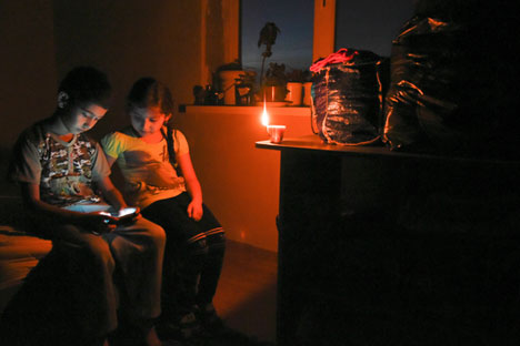 Ethnic Crimean Tatar children play on a cell phone by candlelight at their home in a village outside Simferopol after a power failure,  Crimea, Nov. 22, 2015.