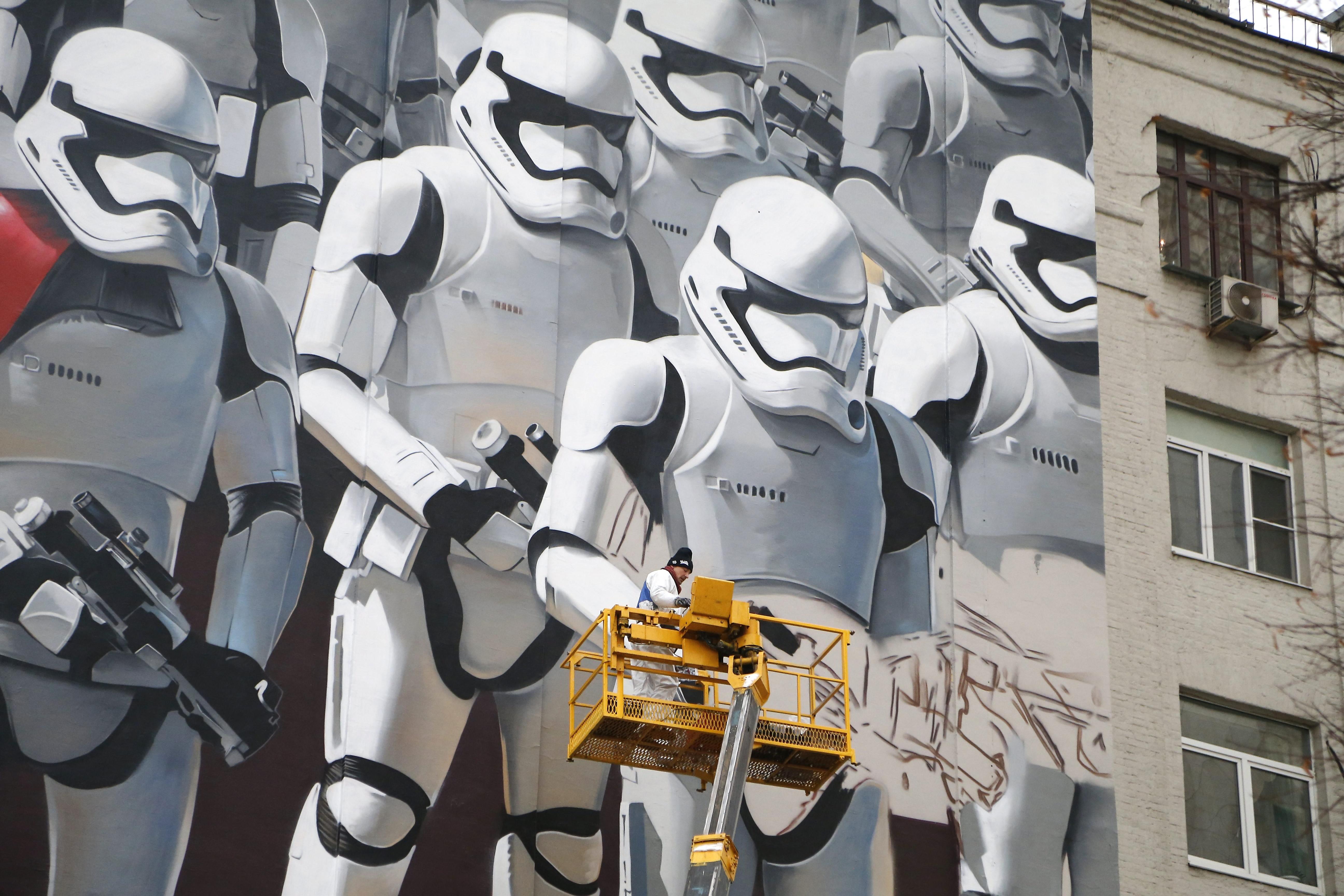 """Уметникот Артур Кашак црта графити на војници од Империските вооружени сили од филмскиот серијал """"Војна на ѕвездите"""" на фасадата на една зграда во Москва, Русија. Кашак го создава своето дело по повод претстојната руска премиера на новото продолжение од филмот """"Војна на ѕвездите 7: Будење на силата""""."""