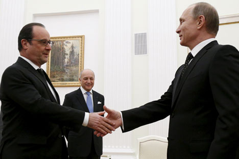 Russia's President Vladimir Putin shakes hands with his French counterpart Francois Hollande, as members of their delegations surround them during a meeting at the Kremlin in Moscow, Nov. 26, 2015.