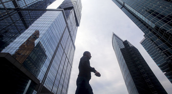 "A man walks in front of the skyscrapers of the International Business Center also known as ""Moskva-City"" in Moscow"