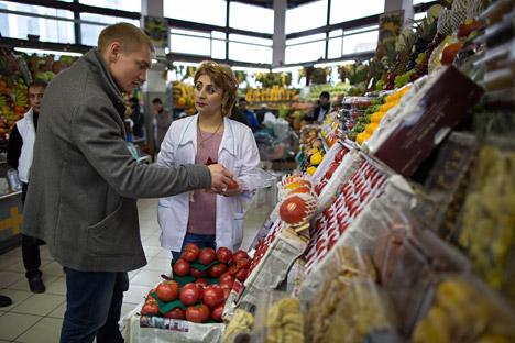 Seorang pedagang membantu seorang pembeli memilih tomat di pasar Dorogomilovsky di Moskow, Rusia, Jumat, 27 November 2015.