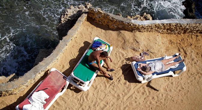 Para turis berjemur di pesisir Laut Merah, di hotel yang menampung wisatawan yang tengah menunggu dievakuaao dari kota Sharm el-Sheikh, Sinai selatan, Mesir, Sabtu (7/11). Rusia menangguhkan semua penerbangan ke Mesir, bersama Inggris, yang mengeluarkan larangan penerbangan ke kota resor tersebut menyusul kecelakaan pesawat minggu sebelumnya di Sinai. Pesawat sewaan kosong telah diterbangke ke resor tersebut untul menjemput para turis Rusia dan Inggris yang masih berada di sana.