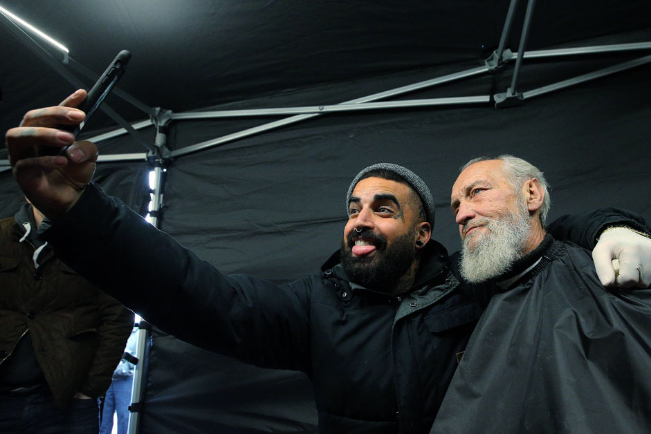 Australia's Nasir Sobhani (left) also known as the Streets Barber takes a photograph of a homeless man after giving him a haircut at Nochlezhka night shelter and rehabilitation center in St. Petersburg.