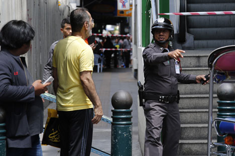 A Royal Thai police officer tells locals and tourists to leave the scene after a suspicious package was detected near a skytrain (elevated light rail) station in downtown Bangkok, Thailand, 19 August 2015.