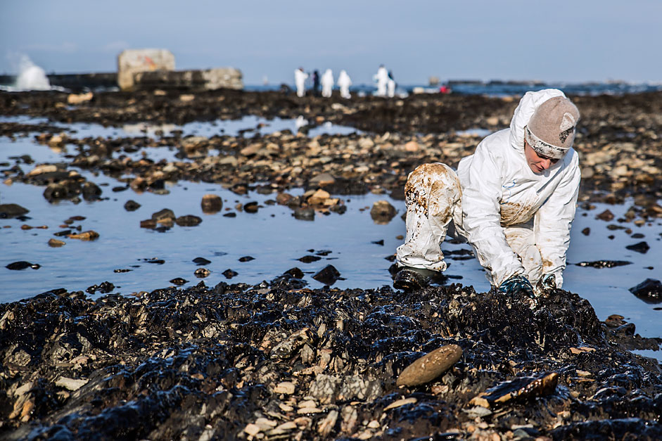 A volunteer cleans up oil products from the coastal rocks in Nevelsk, Sakhalin Region.