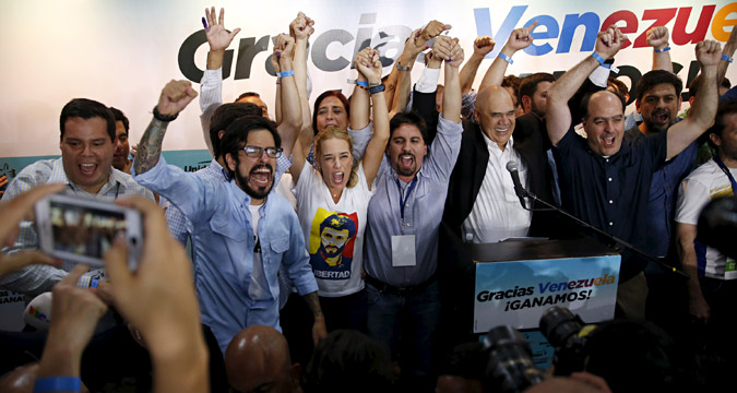 Lilian Tintori (C), wife of jailed Venezuelan opposition leader Leopoldo Lopez, celebrates with candidates of the Venezuelan coalition of opposition parties (MUD) during a news conference on the election in Caracas early Dec. 7, 2015.