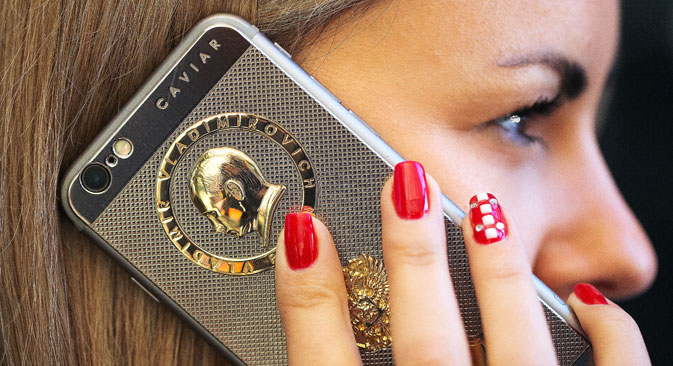 The profile of Vladimir Putin, Russia's president, sits above the coat of arms of the Russian Federation on the rear casing of an 18 carat gold plated 'Ti Gold Supremo Putin' bespoke Apple Inc. iPhone 6s as an employee demonstrates holds it to her ear at the Caviar Boutique at the Zhukovka Plaza shopping centre in Moscow, Russia, on Wednesday, Oct. 21, 2015. Russian policy makers have struggled to concoct the right policy mix to steer the country out of its longest recession in two decades.