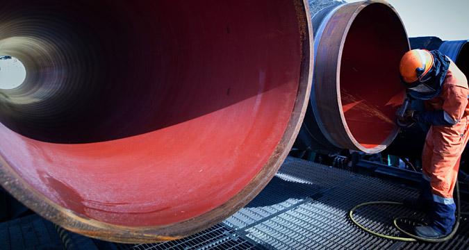 Operaio al lavoro davanti alle tubature di un gasdotto.