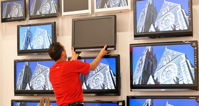 A worker installs a flat screen LCD TV set of Toshiba
