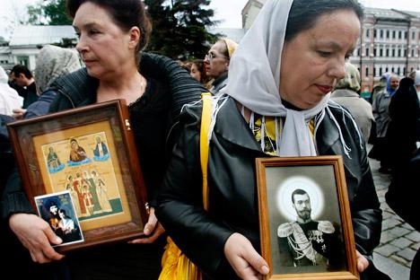 Des femmes tiennent des icônes représentant la famille des Romanov canonisée en 1981.