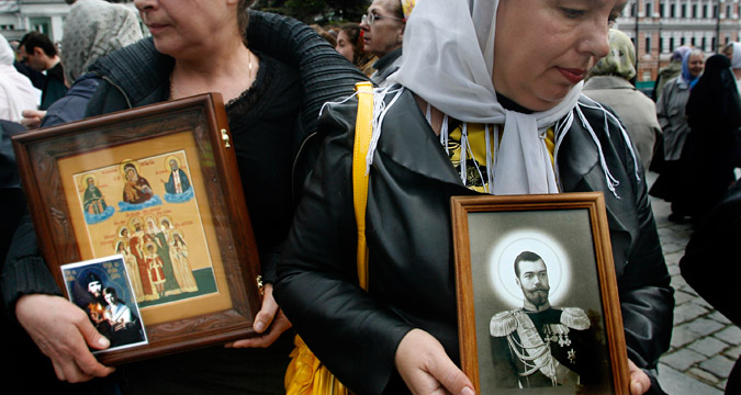 Women hold icons depicting the last Russian Czar Nicholas II