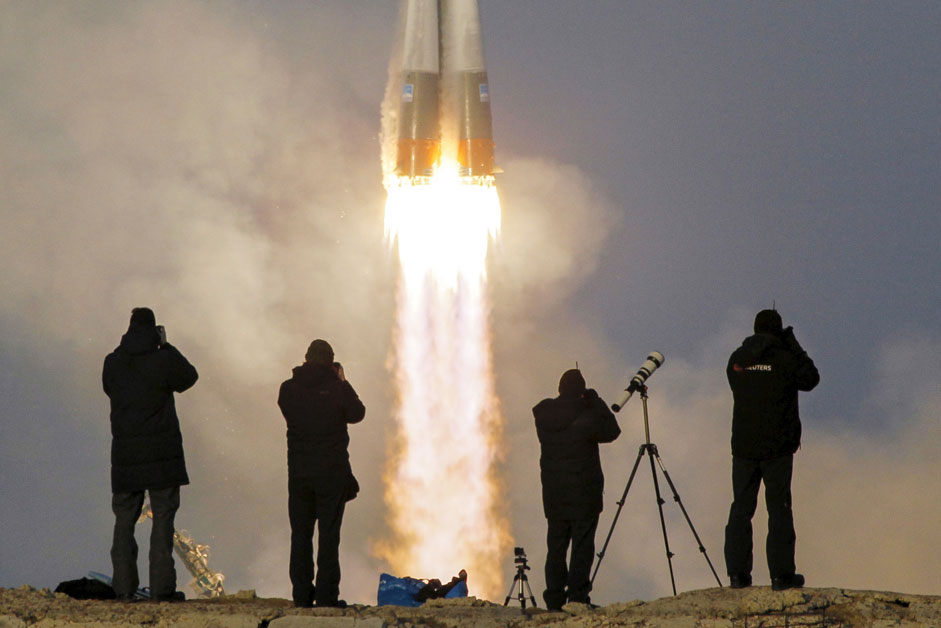 Photographers take pictures as the Soyuz TMA-19M spacecraft carrying the crew of Timothy Peake of Britain, Yuri Malenchenko of Russia and Timothy Kopra of the U.S. as it blasts off to the International Space Station (ISS) from the launchpad at the Baikonur cosmodrome, Kazakhstan