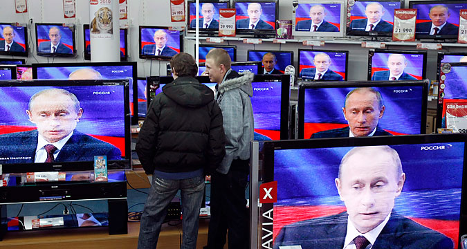 Men look at a television screening of Russia?s Prime Minister Vladimir Putin as he speaks during a question-and-answer show at a Russian state TV channel, at an electronics shop in Moscow December 3, 2009. Putin on Thursday said the Cold War-era Jackson-Vanik amendment that tied U.S. trade relations to emigration rights for religious minorities was an anachronism and hindered Russia's entry to the World Trade Organization (WTO).