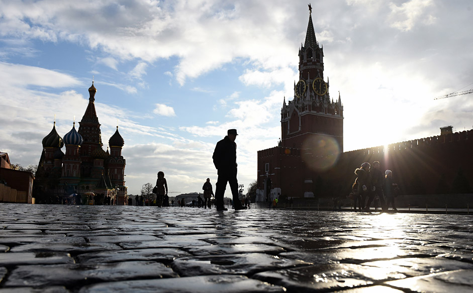 People walk across Red Square, with the Kremlin's Spasskaya (Saviour) Tower (R) and St. Basil's Cathedral (L) seen in the background, in central Moscow on December 22, 2015. The temperatures in the Russian capital reached today 6 C (42 F).