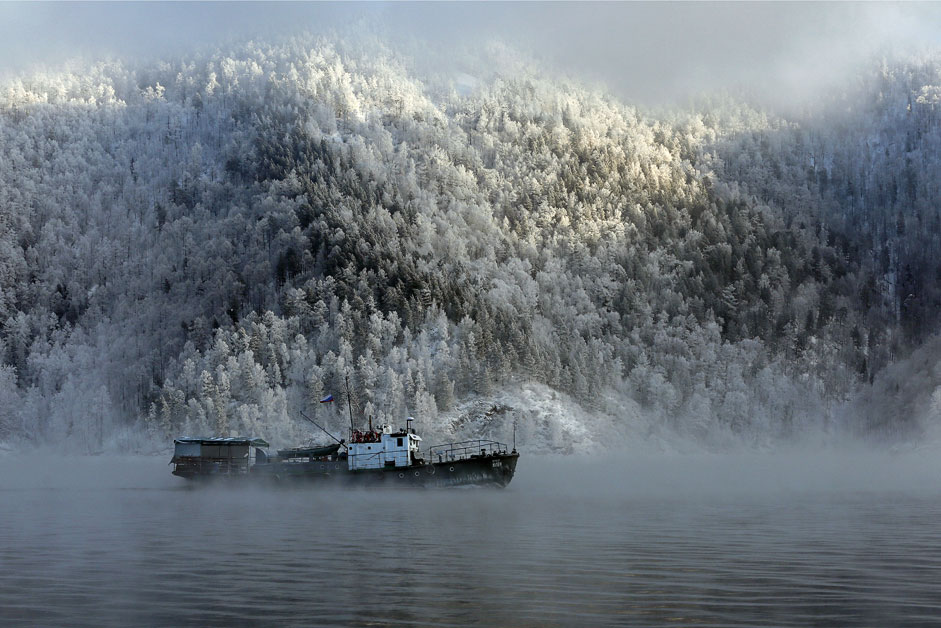 A motor boat sails along the Yenisei River, with the air temperature at about minus 20 degrees Celsius (minus 4 degrees Fahrenheit), outside the Siberian city of Krasnoyarsk, Russia
