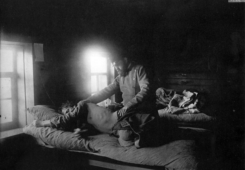 Un médecin examine un homme malade du typhus dans le village de Nakroussov.
